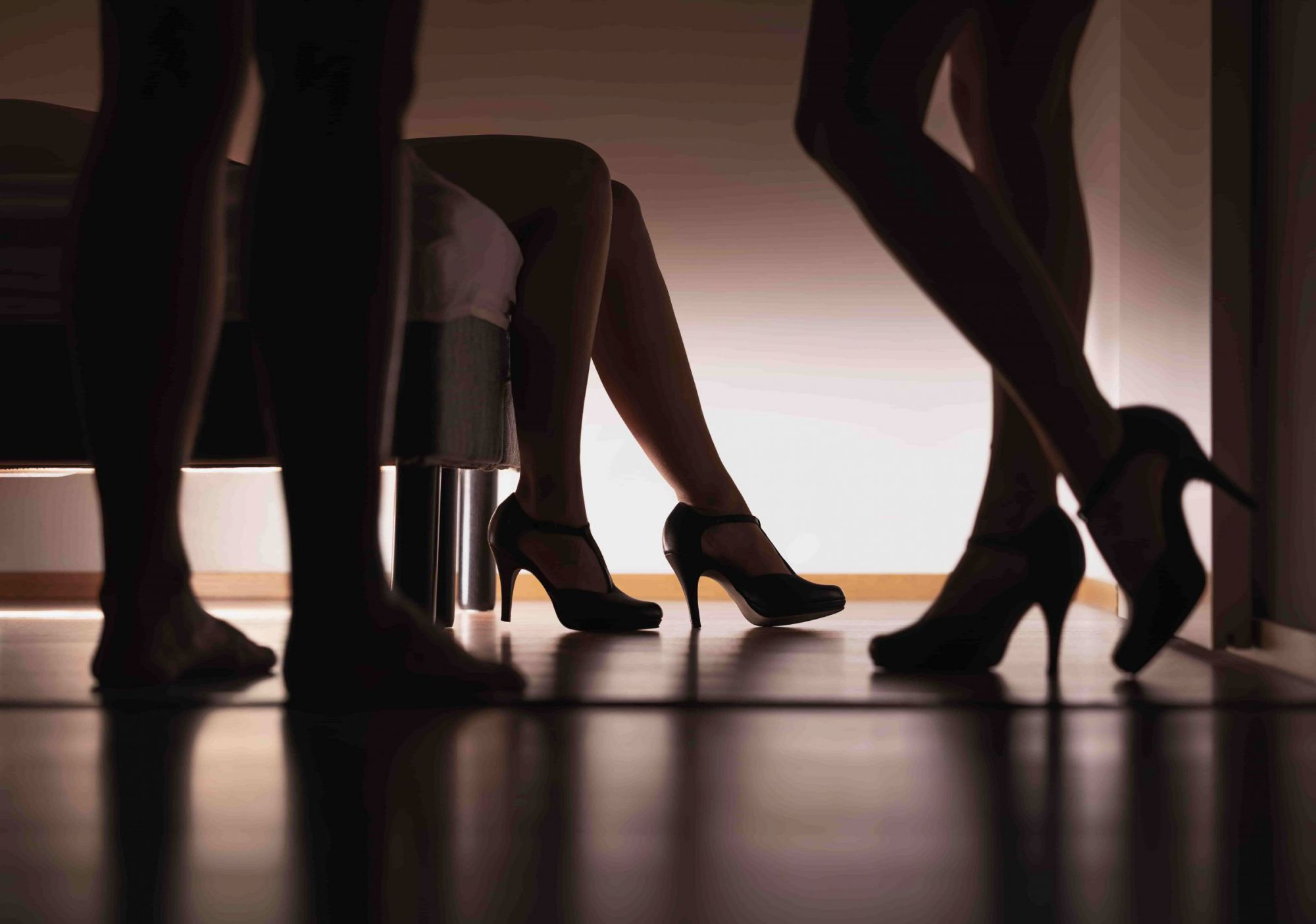 man and womens in heels legs by a bed